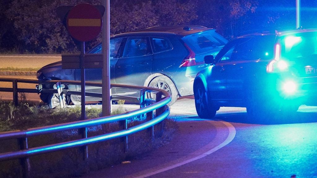 En polisbil står framför en vanlig bil på en väg.