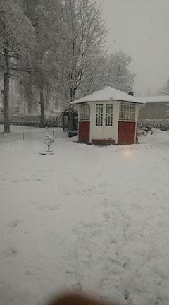 Bild på snö och ett röd-vitt hus