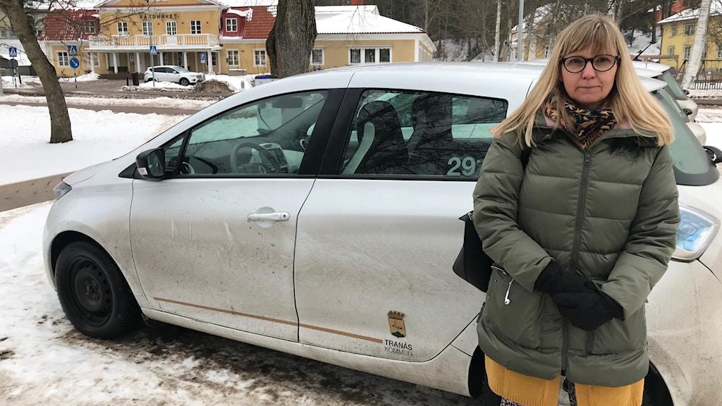 Kvinna står vid en bil