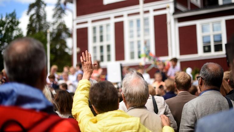 Personer står och tittar och vinkar mot en röd byggnad som barn står framför.