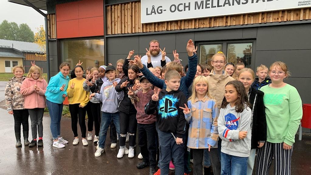 bild på massa barn ståendes framför skola.