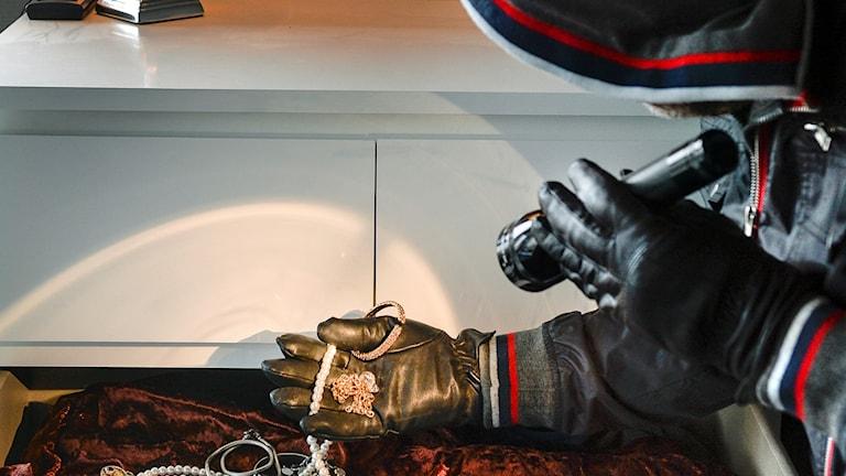 En tjuv tar smycken ur en byrålåda. Foto: Anders Wiklund/TT.