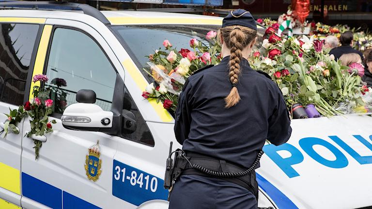 En polis lägger blommor på en polisbil. Foto: Christine Olsson/TT.