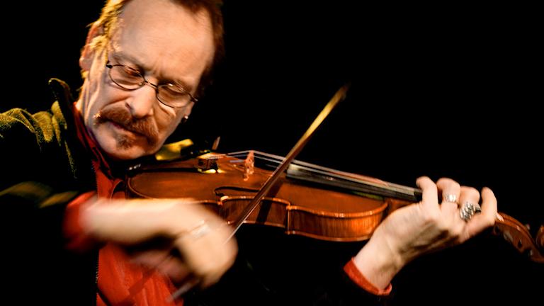 Man spelar fiol och blundar