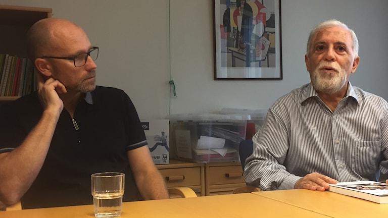 Två män sitter bakom ett kontorsbord. En kontorsvägg finns några meter bakom.