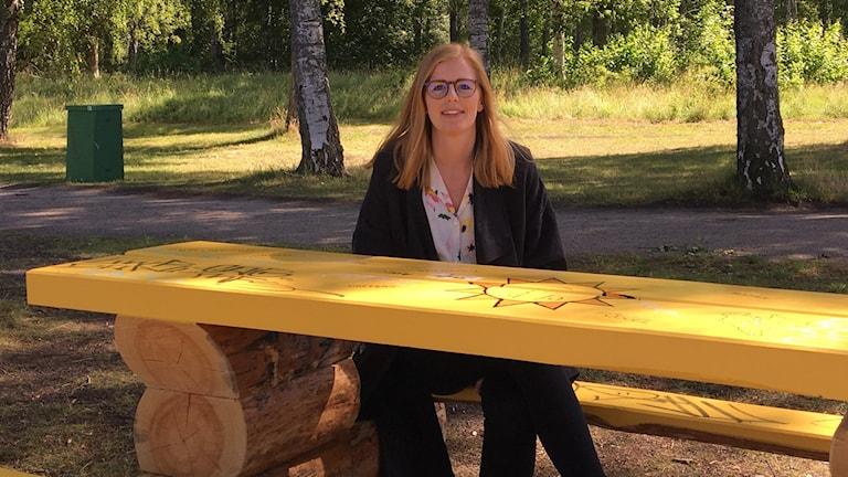 En tjej som sitter vid en gul bänk.