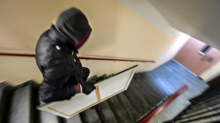 Maskerad man bär tavla nerför trappa.