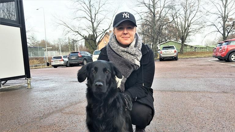 Emelie Danielsson och hunden Tage på parkeringsplats. Foto: Sara Lindroos/Sveriges radio