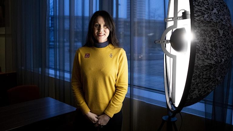 Paralympikern Anna Beck från Kil poserar i gul tröja vid en stor lampa.