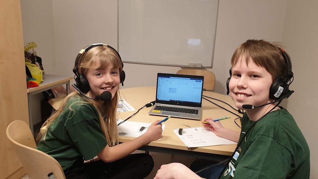 Två barn i gröna tröjor sitter vit en skolbänk och ser glada ut.
