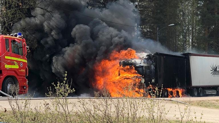 brinnande lastbil intill en skog, räddningstjänst på plats