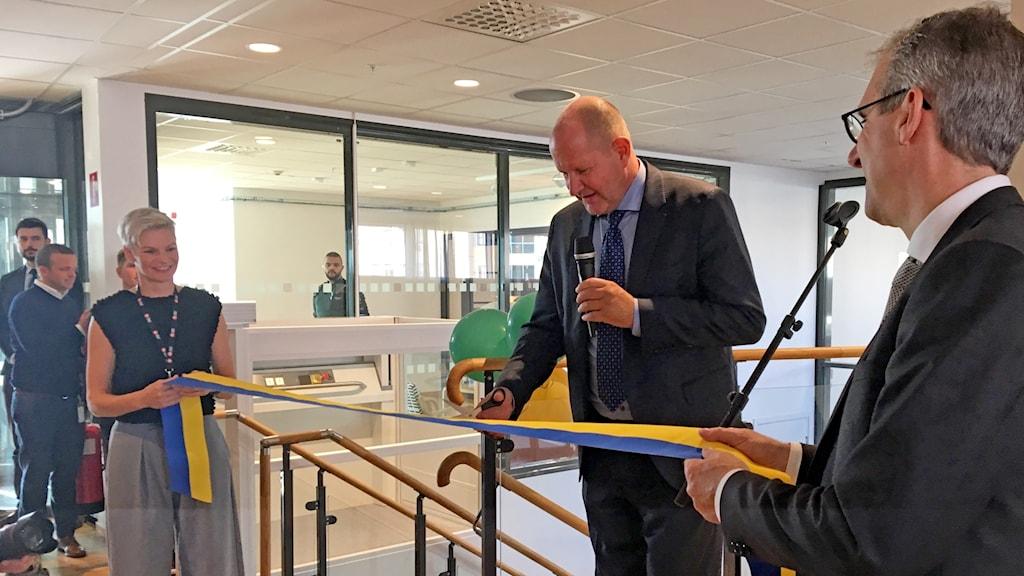 En man klipper ett blågult band i ett kontor.