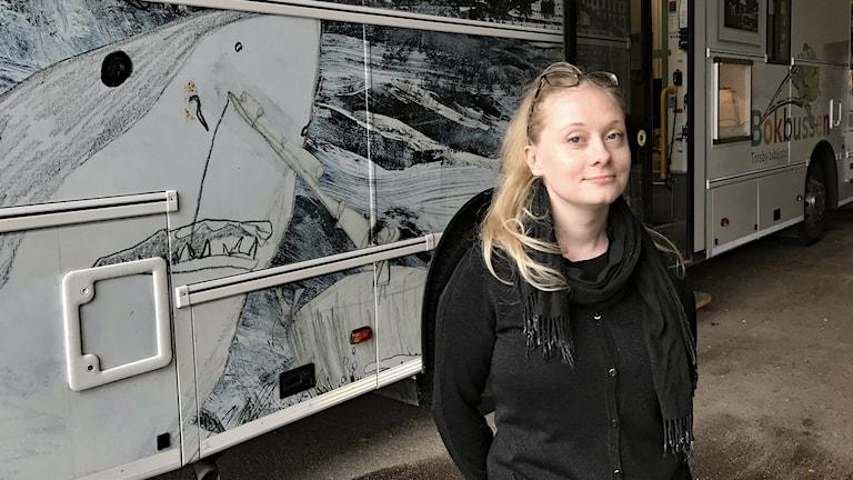 Nora Bütter framför en bokbuss. Foto: Per Larsson/Sveriges Radio.