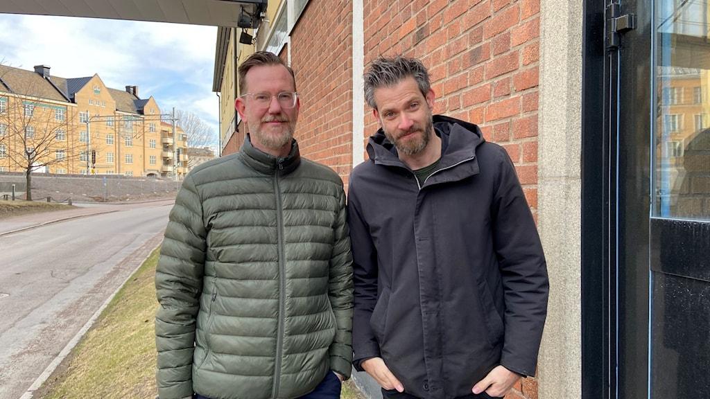Två män står vid en väg bredvid ett tegelhus.