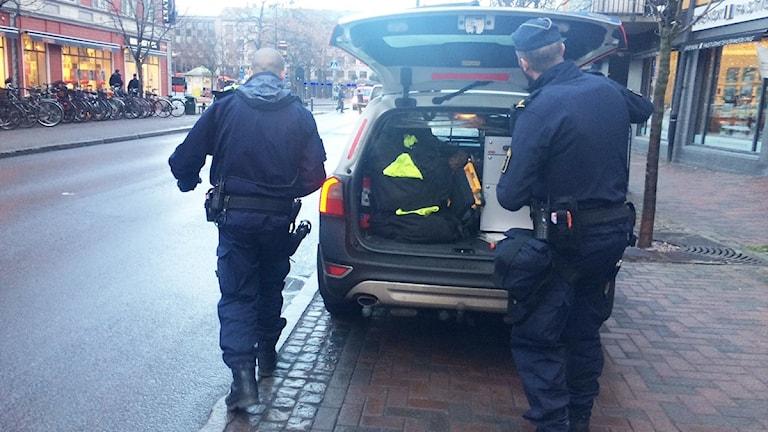 Poliser vid en polisbil. Foto: Jenny Tibblin/Sveriges Radio.