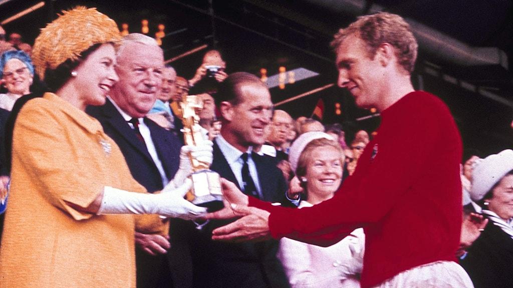 Drottning Elizabeth II ger VM-bucklan till Englands lagkapten Bobby Moore efter VM-finalen 1966. Turneringen bojkottades av hela den afrikanska kontinenten. Foto: AP photo.