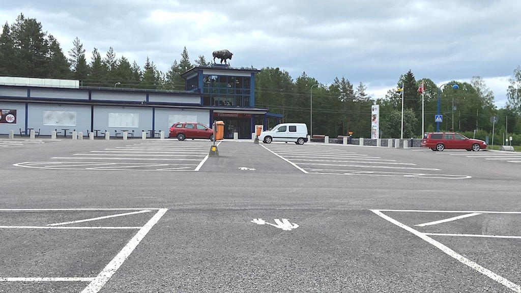 tre bilar på en nästan tom parkering