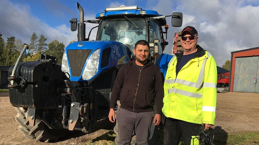 två män framför traktor
