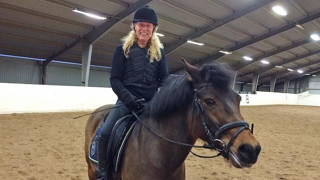 Marita Rantanen sittandes på sin häst. Foto: Hedvig Nilsson/Sveriges Radio.