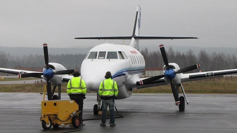 Två män i lysgula jackor framför ett flygplan på landningsbanan vid Torsby flygplats.Foto: Lennart Nordenstein/SR.