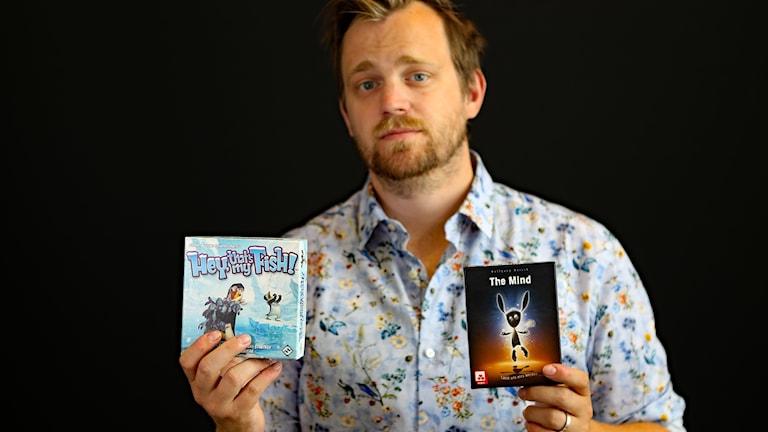 P4 Värmlands producent Jonas Hansson håller upp de två spelen som han tipsar om. Foto Örjan Bengtzing/Sveriges Radio.