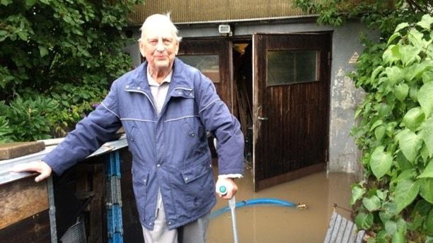Man framför översvämmad garagenedfart