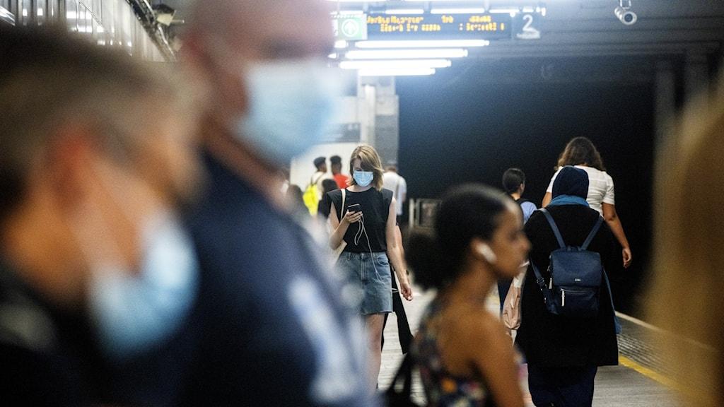 Personer med munskydd i kollektivtrafiken.