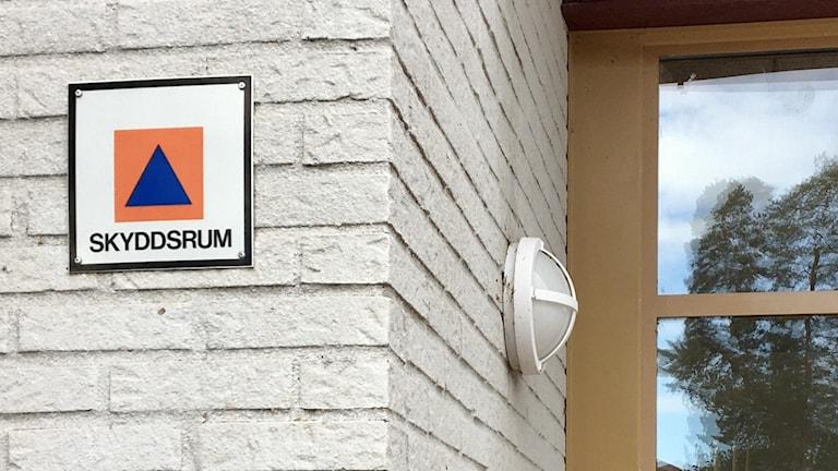 Skylten som markerar skyddsrum på en vt tegelvägg