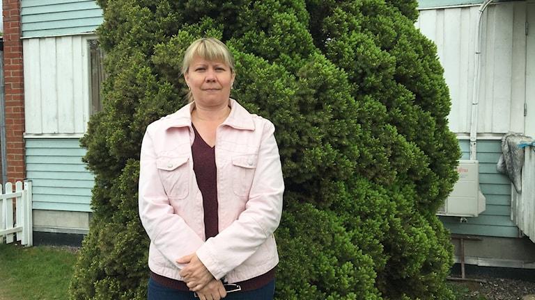 kvinna står i trädgård framför en jättegran