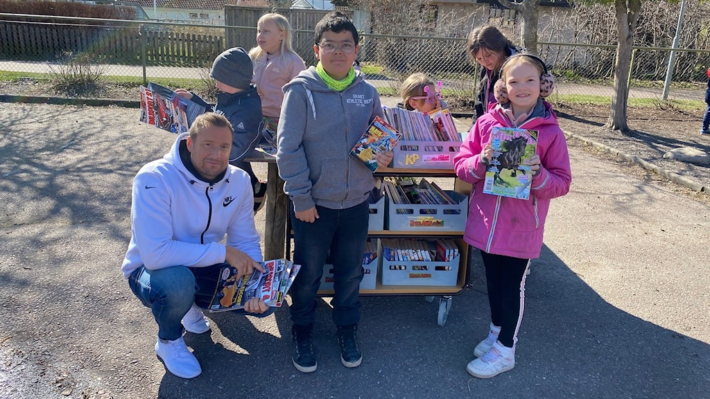 En lärare och ett antal barn med böcker på en skolgård.