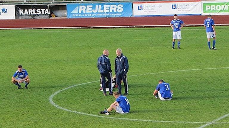 Fotbollsspelare sitter på planen efter matchslut: Foto: Joakim Lindström/Sveriges Radio.