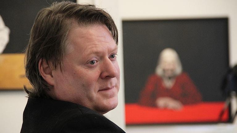 Joakim Johansson, i bakgrunden målning av Lena Cronqvist. Foto: Lars-Gunnar Olsson/Sveriges Radio.