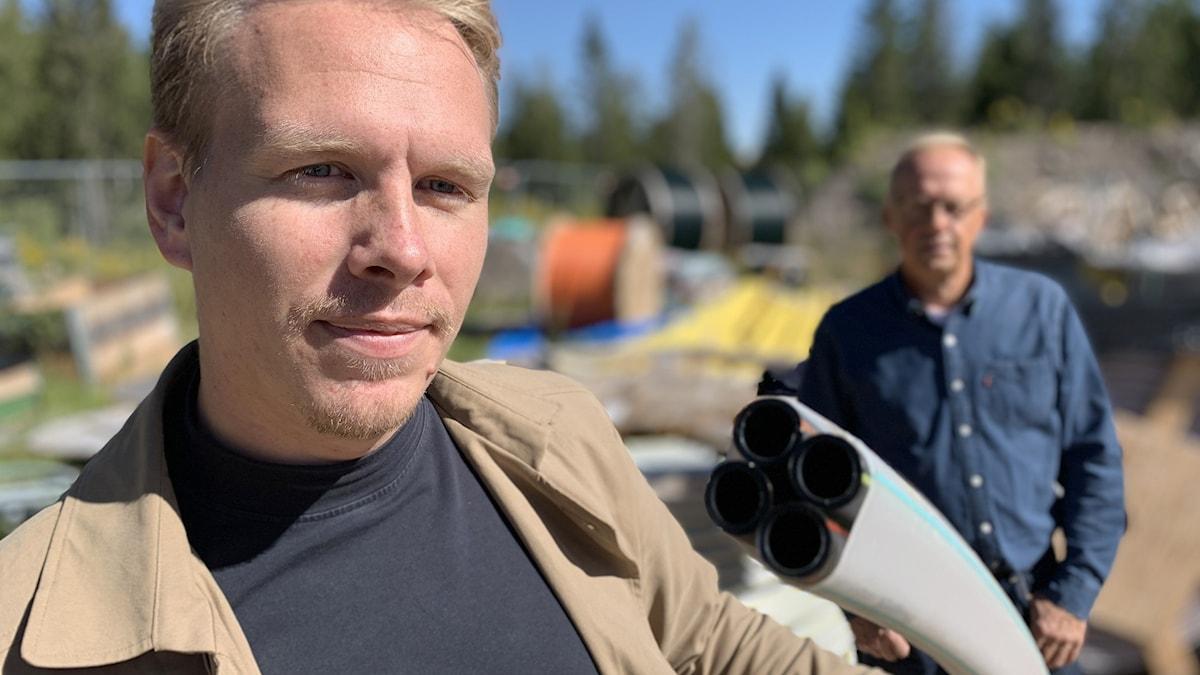 en man håller i en fiberkabelskanal, en annan man syns i bakgrunden