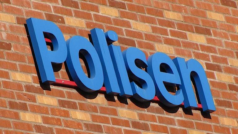 Polisskylt på vägg. Foto: Lars-Gunnar Olsson/Sveriges Radio.