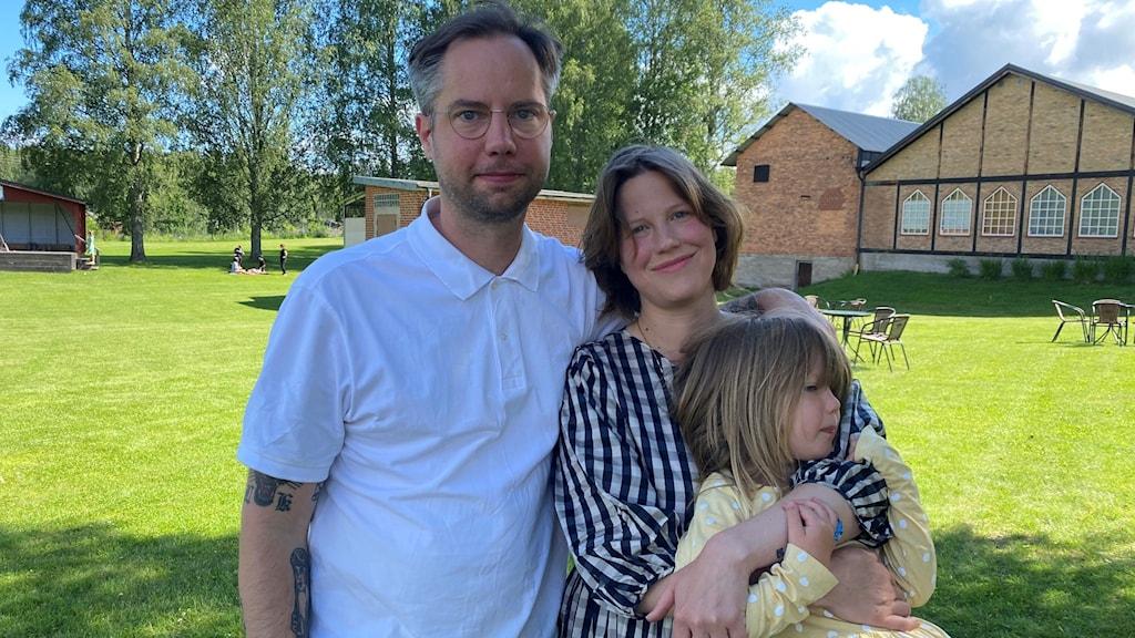 En man och en kvinna och ett barn står utomhus.