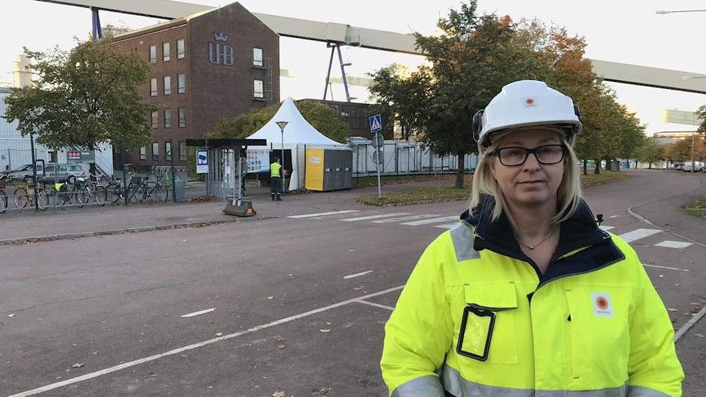 Kvinna i reflexjacka och hjälm framför bruket på Skoghall. Foto: Per Larsson/Sveriges Radio.
