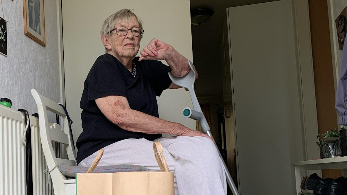 Äldre kvinna sitter i sin hall med matkassar bredvid sig, stödd på en krycka. Foto: Amanda Moln/ Sveriges Radio.