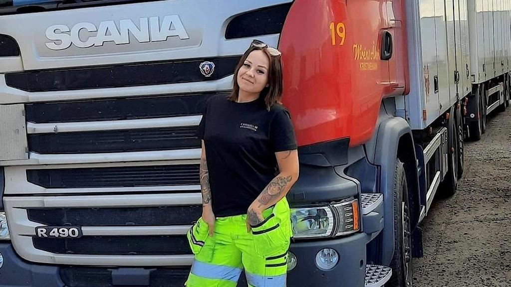 En kvinna står framför en lastbil.