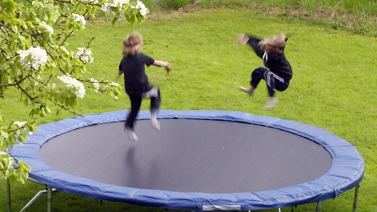 två barn studsar på en studsmatta