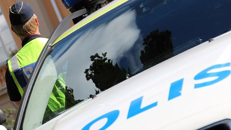 Polisbil och en polis. Foto: Lars-Gunnar Olsson/Sveriges Radio.
