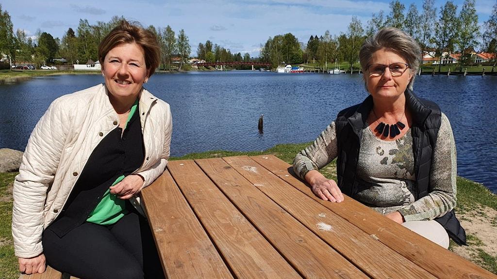 två damer vid ett bord vid en sjö