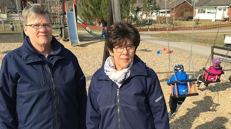 Dagbarnvårdarna Anita Larsson, till vänster, och Eva-Lena Fredholm, i en lekpark i Forshaga. I bakgrunden skymtar ett par barn smo gungar. Foto: Magnus Hermansson/Sveriges Radio.