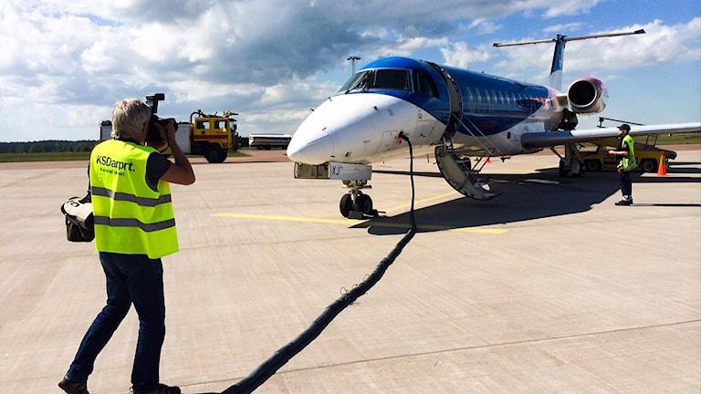 Man fotograferar flygplan på landningsbanan
