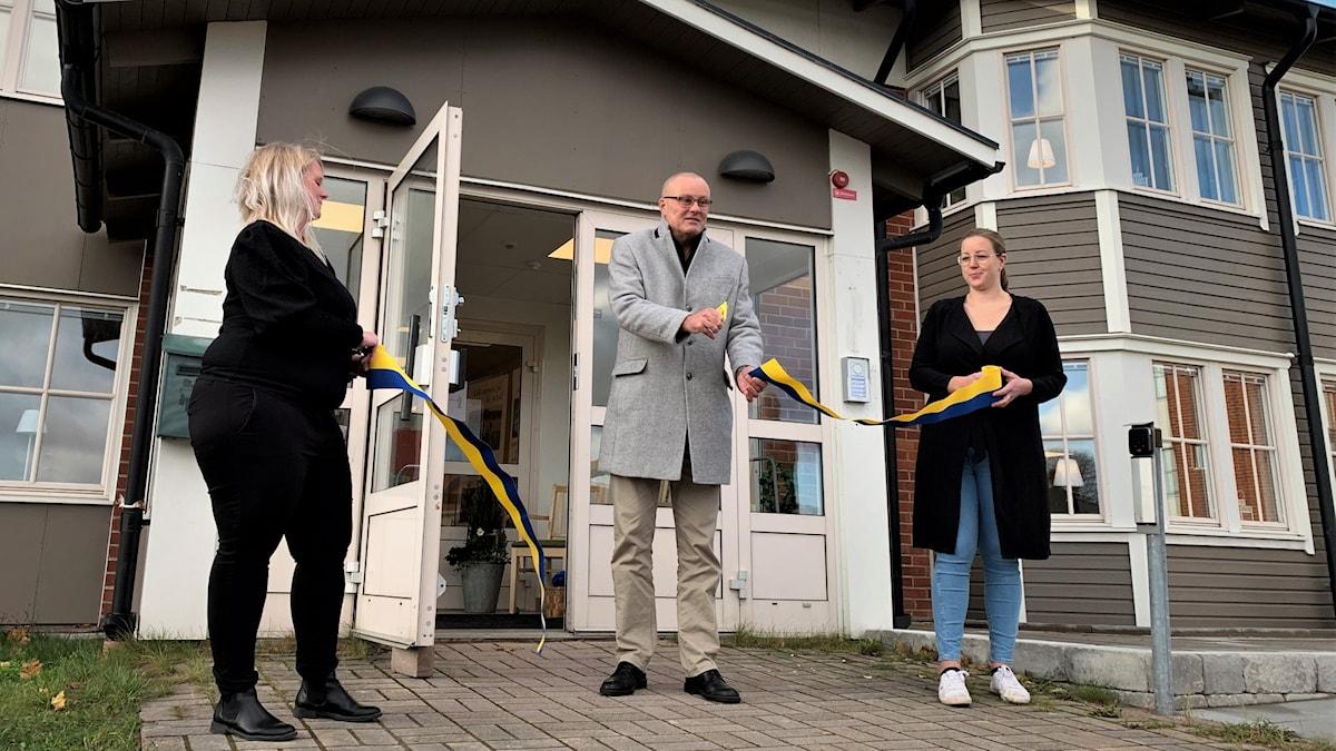 man klipper band som två kvinnor håller utanför nybyggt hus