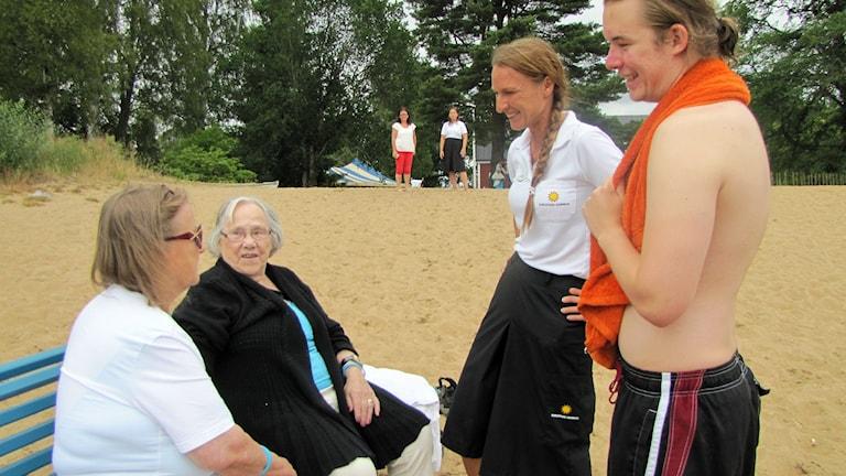 Pensionärer och personal på strand. Foto: Carol Atallah/Sveriges Radio.