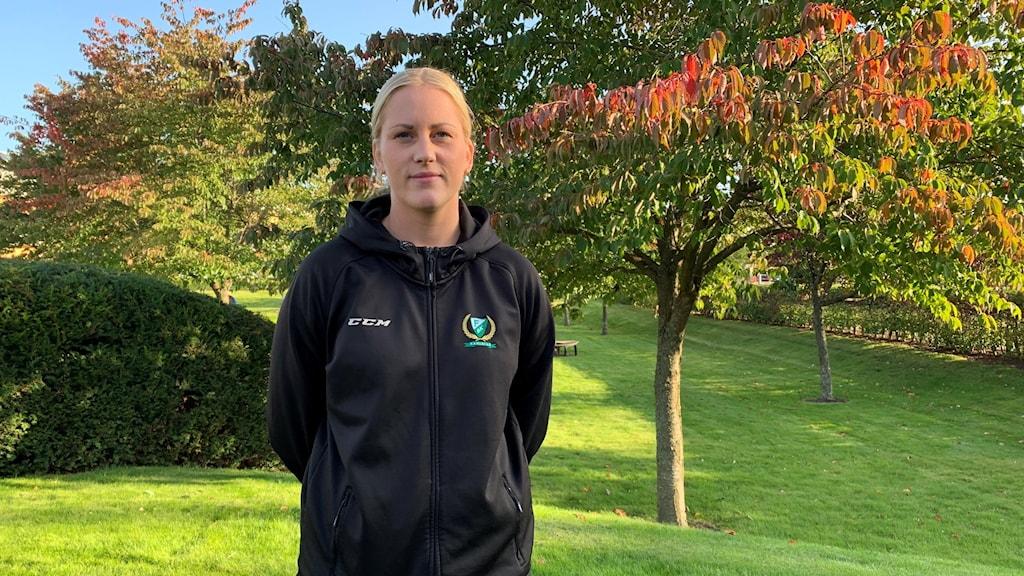 Jennifer Axelsson som är assisterande lagkapten i Färjestad står utomhus. Bakom henne är träd med rödgrönablad.