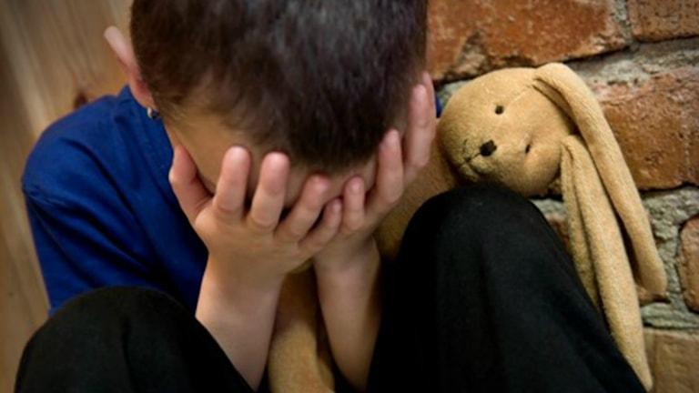 Ett barn håller händerna över ansiktet. Foto: Claudio Bresciani/TT.