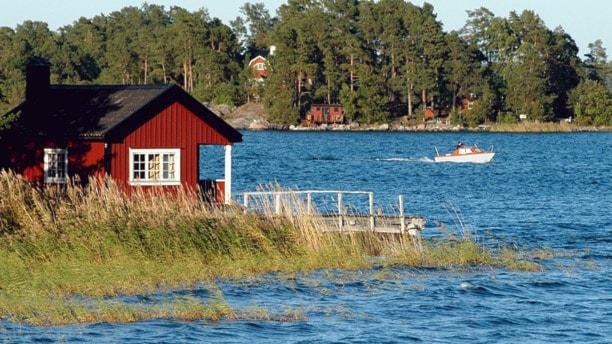 Röd stuga och båt i vattnet vid skärgård. Foto: TT