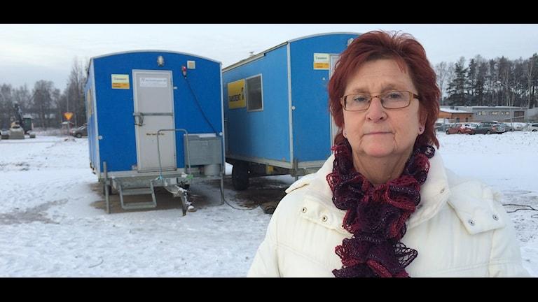 Agneta Andersson från föreningen Stöd för Hemlösa Värmland framför de två baracker som ordnats åt de hemlösa eu-migranterna.
