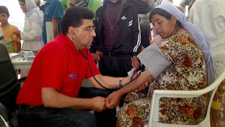 Lokman Atroshi tar blodtryck på en kvinna. Foto: Lokman Atroshi.